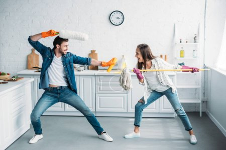 couple having fun and pretending fight with cleaning tools in kitchen