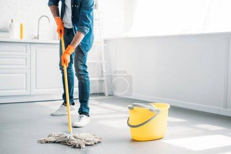 Photo pour Image recadrée de l'homme, nettoyage de plancher dans la cuisine avec vadrouille - image libre de droit