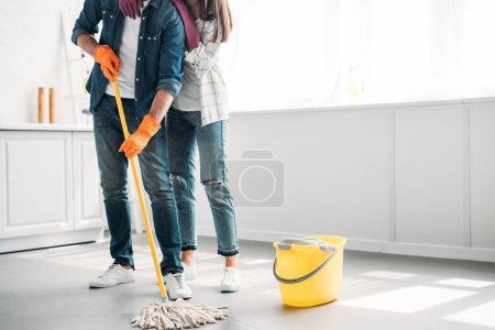 Photo for Cropped image of boyfriend cleaning floor in kitchen with mop and girlfriend hugging him - Royalty Free Image