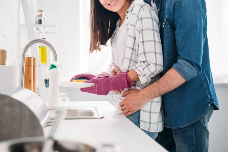 cropped image of girlfriend washing dishes and boyfriend hugging her in kitchen