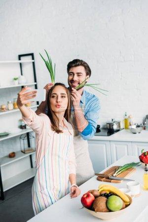 Photo pour Couple prenant selfie tout en s'amusant pendant la cuisson en cuisine - image libre de droit
