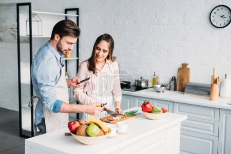 Photo for Girlfriend cutting vegetables and boyfriend holding smartphone in kitchen - Royalty Free Image