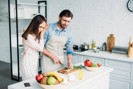 boyfriend cutting onion and crying girlfriend leaning on him in kitchen