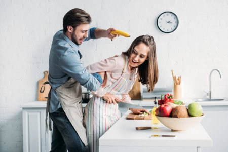 Photo for Girlfriend cutting vegetables and boyfriend having fun with banana gun in kitchen - Royalty Free Image