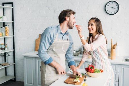 Freund schneidet Gemüse und Freundin füttert ihn in Küche mit Tomaten