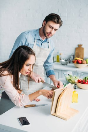 Photo for Boyfriend cutting vegetables and girlfriend reading recipe in kitchen - Royalty Free Image