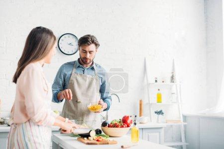 girlfriend cutting vegetables and boyfriend adding corn to salad in kitchen