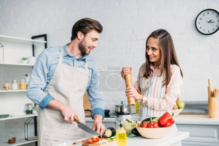 Photo for Boyfriend cutting vegetables and girlfriend adding spices to salad in kitchen - Royalty Free Image