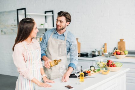 Photo for Boyfriend pouring wine into glass and looking at girlfriend in kitchen - Royalty Free Image