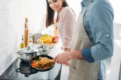 """Постер, картина, фотообои """"обрезанное изображение бойфренд жарки овощей на электрическая плита в кухне"""""""