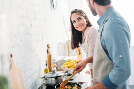 Photo for Boyfriend frying vegetables on frying pan in kitchen and looking at smiling girlfriend - Royalty Free Image