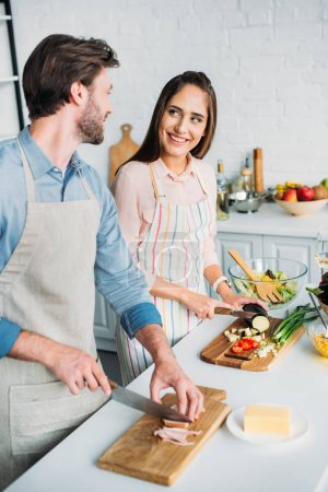 smiling couple cooking and cutting vegetables with meat in kitchen