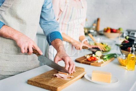 cropped image of couple cooking and cutting vegetables with meat in kitchen