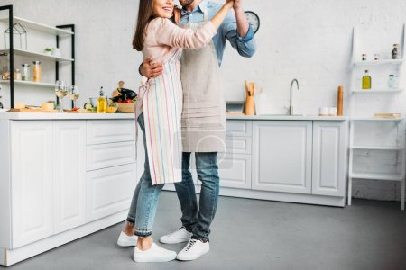 cropped image of couple hugging and dancing in kitchen