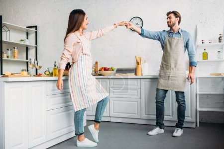 couple holding hands and dancing in kitchen