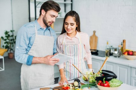 Photo for Couple looking at tablet with recipe while cooking in kitchen - Royalty Free Image