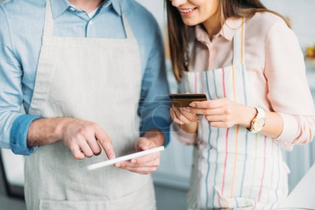 cropped image of couple shopping online with tablet and credit card in kitchen