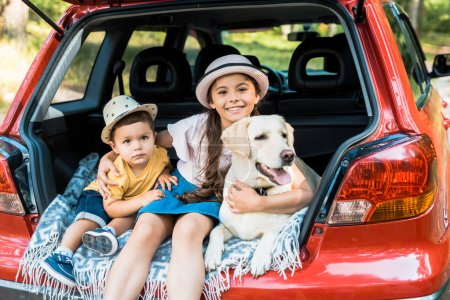 siblings sitting on car trunk with labrador dog