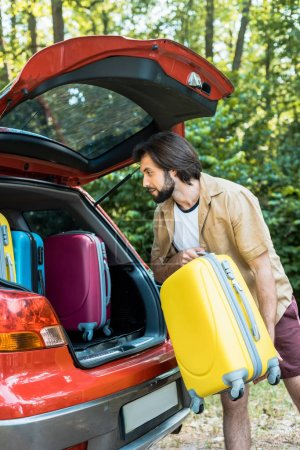 Photo for Handsome man packing car trunk with travel bags - Royalty Free Image
