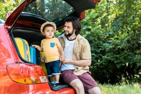 smiling father and son sitting on car trunk in forest