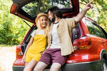 Photo pour Petit ami pointant sur quelque chose de petite amie tout en étant assis sur le coffre de voiture - image libre de droit