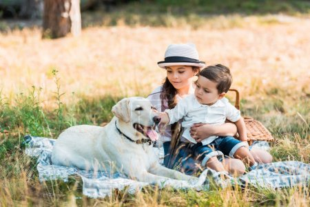 brother and sister sitting on blanket with labrador dog
