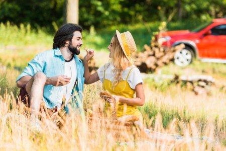 girlfriend feeding boyfriend with loaf of bread at picnic