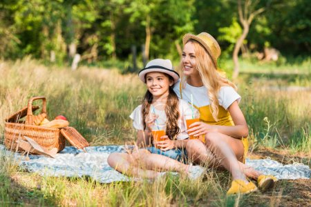 mother and daughter sitting on blanket at picnic and holding glasses of juice