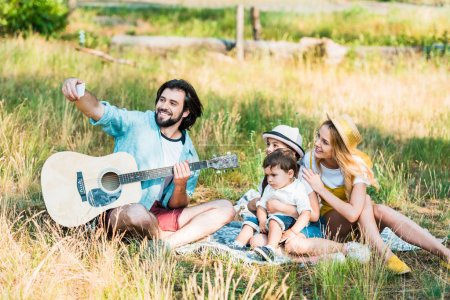 father taking selfie of family with smartphone at picnic
