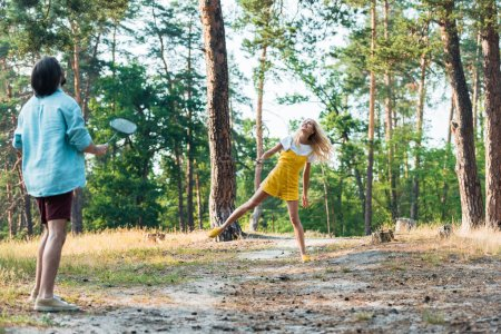 Photo for Couple playing badminton in forest at weekend - Royalty Free Image