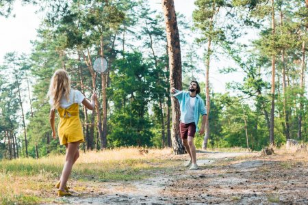 young couple playing badminton outdoors
