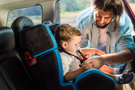 handsome father fastening son in safety seat in car