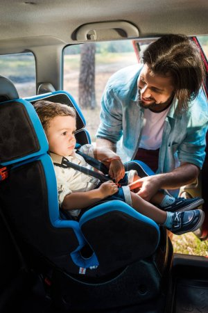 smiling father fastening son in safety seat in car