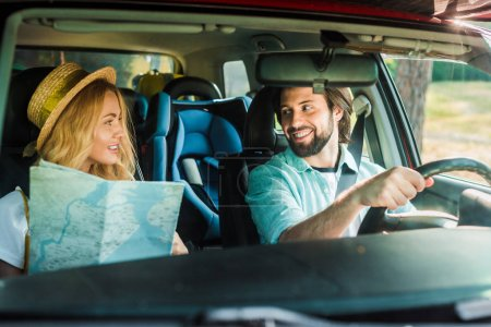 happy couple traveling by car with map