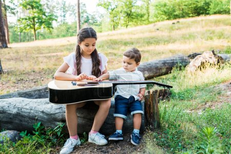 siblings sitting on log at lawn with acoustic guitar
