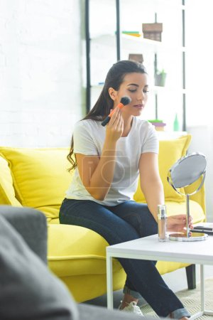 young attractive woman looking at mirror while doing makeup on sofa at home
