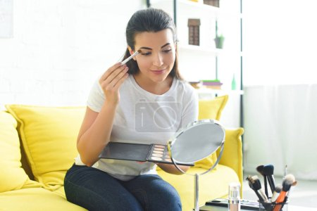 young woman with makeup palette in hands applying eye shadows while doing makeup on sofa at home