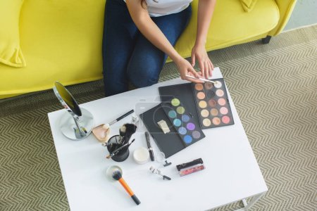 cropped shot of woman with makeup brush sitting on sofa at coffee table with cosmetics for makeup at home