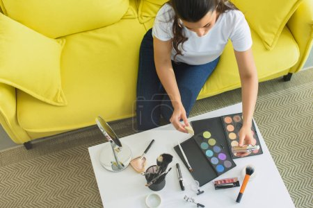overhead view of woman sitting on sofa at coffee table with cosmetics for makeup at home