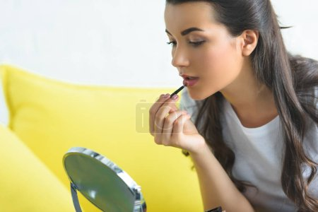 side view of young woman applying lipstick while doing makeup on sofa at home