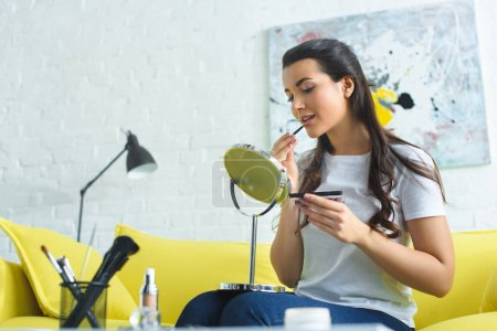 young woman applying lipstick while doing makeup on sofa at home