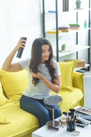 smiling woman applying hair spray to fix hairstyle while sitting on sofa at home