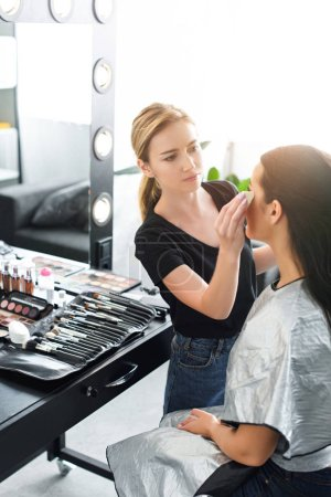 side view of beautiful young woman getting makeup done by focused makeup artist