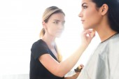 selective focus of beautiful young woman getting makeup done by focused makeup artist
