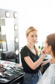 selective focus of young woman getting makeup done by makeup artist