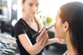 selective focus of woman getting makeup done by makeup artist