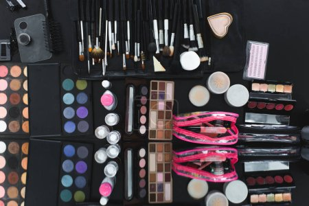 top view of arranged various makeup equipment on black tabletop