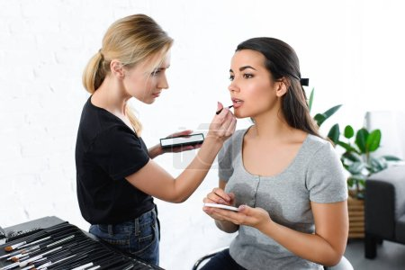 attractive woman with smartphone getting makeup done by makeup artist