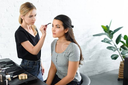 pensive woman getting makeup done by focused makeup artist with brush