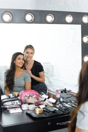 mirror reflection of beautiful young woman and smiling makeup artist
